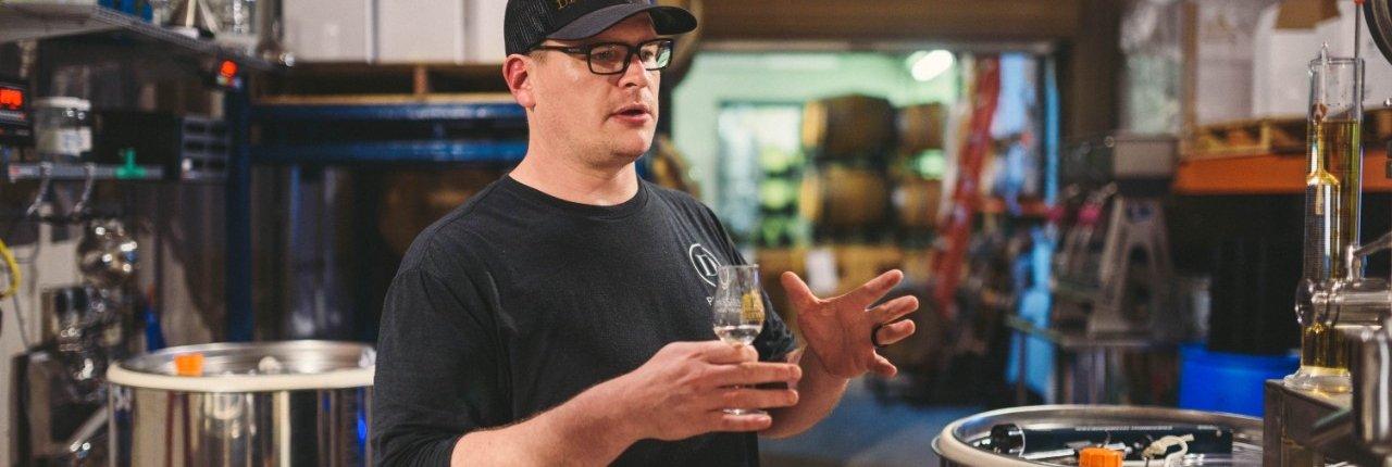 Image of distiller Allan Delmare in the distillery explaining process of distillation